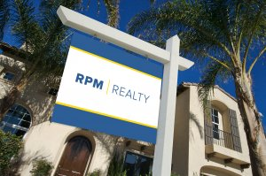 RPM Realty sign hanging in front yard next to palm trees