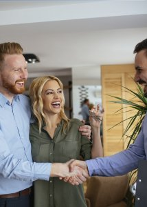 smiling couple shaking hands with a realtor and holding up house keys