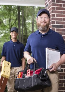 two maintenance workers holding toolkits